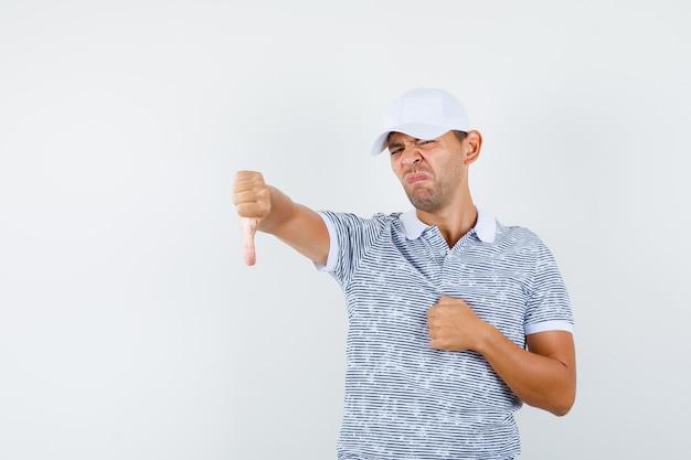 Młody mężczyzna w koszulce i czapce pokazujący kciuk w dół i wyglądający na niezadowolonego