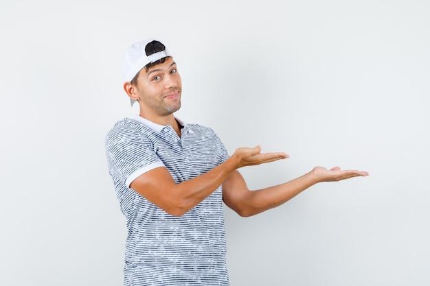 Młody mężczyzna w koszulce i czapce witający lub pokazujący coś i wyglądający na zadowolonego