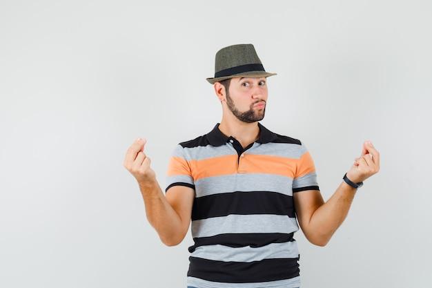 Młody mężczyzna w koszulce, kapeluszu, gestykuluje rękami i palcami i wygląda pewnie, widok z przodu.