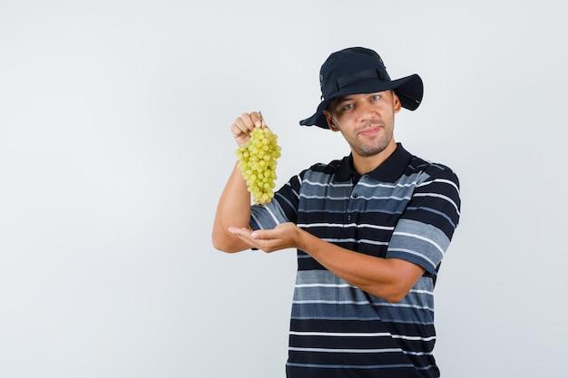 Młody mężczyzna w koszulce, kapeluszu pokazującym grono świeżych winogron i patrzący zadowolony, widok z przodu.