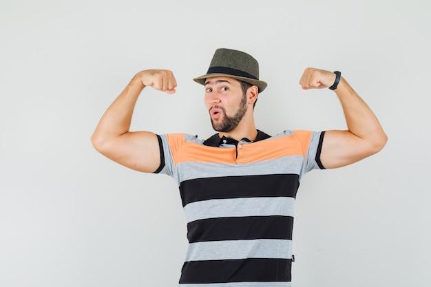 Młody mężczyzna w koszulce, kapeluszu pokazującym mięśnie i wyglądającym potężnie, widok z przodu.