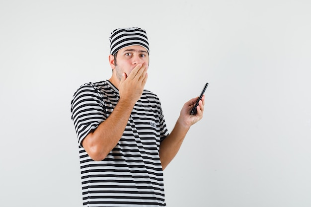 Młody mężczyzna w koszulce, kapeluszu, trzymając telefon komórkowy i patrząc zdziwiony, widok z przodu.