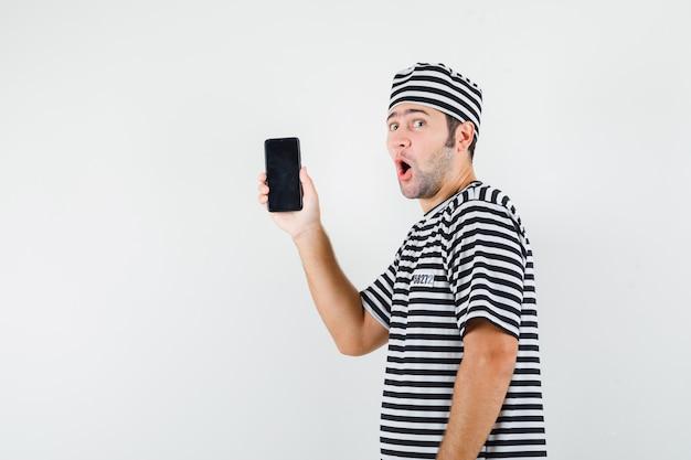 Młody mężczyzna w koszulce, kapeluszu, trzymając telefon komórkowy i patrząc zdziwiony.