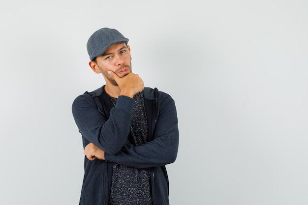 Młody mężczyzna w koszulce, kurtce, czapce stojącej w myślącej pozie i patrząc inteligentnie, z przodu.