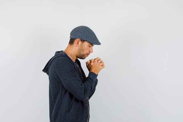 Młody mężczyzna w koszulce, kurtce, czapce, trzymając splecione dłonie w geście modlitwy i wyglądający na spokojnego.