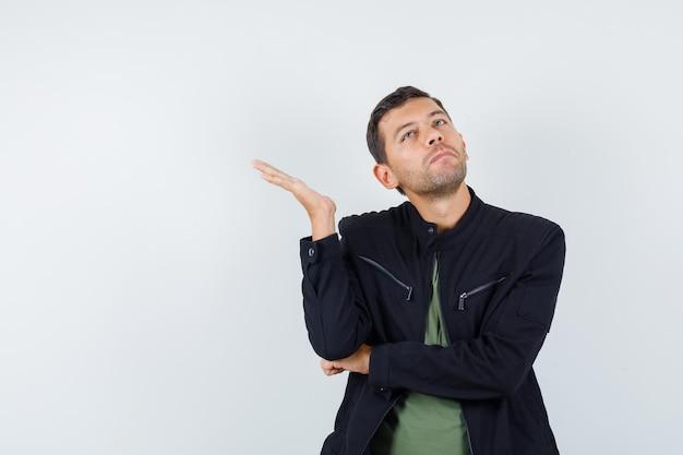 Młody mężczyzna w koszulce, kurtce patrząc w górę z podniesioną dłonią i patrząc zirytowany, widok z przodu.