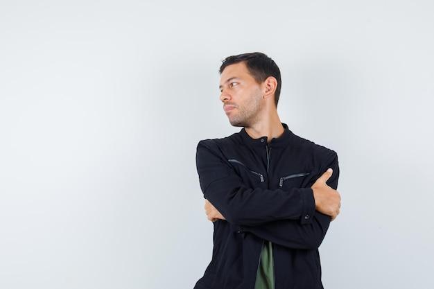 Młody mężczyzna w koszulce, kurtce patrzącej na bok ze skrzyżowanymi rękami i wyglądającym elegancko, widok z przodu.