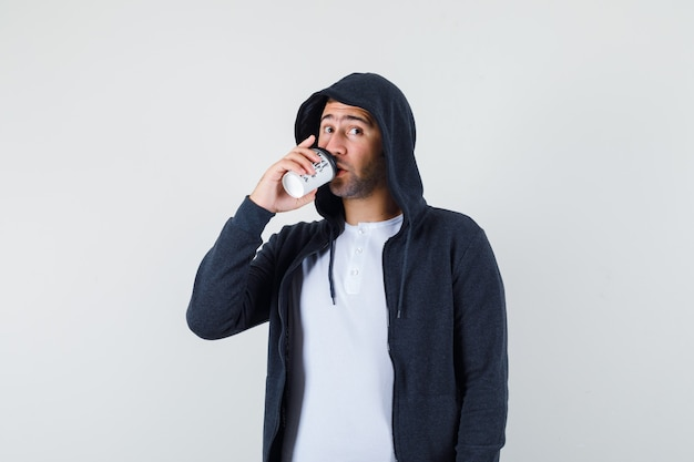 Młody mężczyzna w koszulce, kurtce pije kawę i wygląda przestraszony, widok z przodu.