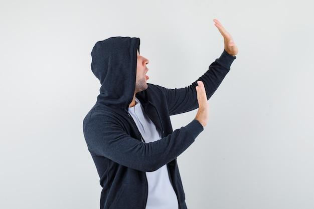Młody mężczyzna w koszulce, kurtce, podnosząc ręce, by się bronić i wyglądający na przestraszonego, widok z przodu.