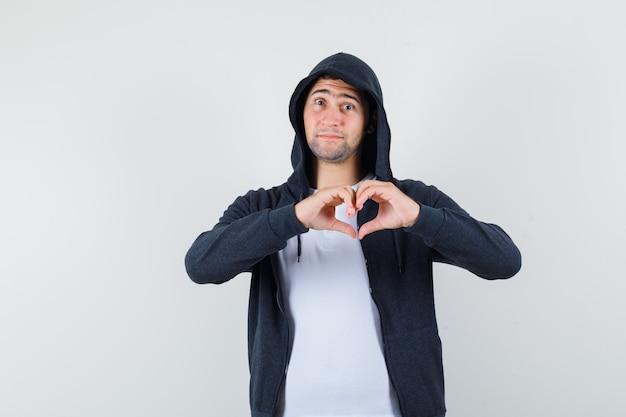 Młody mężczyzna w koszulce, kurtce pokazuje gest serca i wygląda pięknie, widok z przodu.