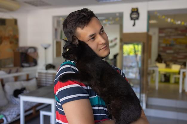 Młody mężczyzna w koszulce trzyma kota