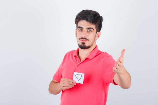 Młody mężczyzna w koszulce trzymając karteczkę podczas podnoszenia ręki w pytający sposób i patrząc pewnie, widok z przodu.