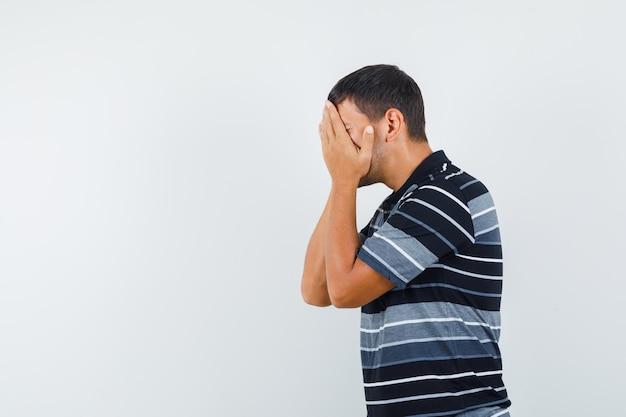 Młody mężczyzna w koszulce trzymając się za ręce na twarzy i patrząc smutny.
