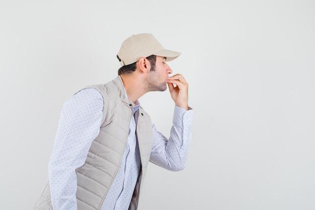 Młody mężczyzna w koszuli, bluzie bez rękawów, czapce pokazującej pyszny gest i patrząc skupiony, widok z przodu.