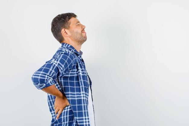 Młody mężczyzna w koszuli cierpi na bóle pleców i wygląda bolesnie.