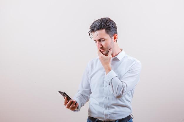 Młody mężczyzna w koszuli, dżinsach, patrzący na telefon komórkowy i zamyślony