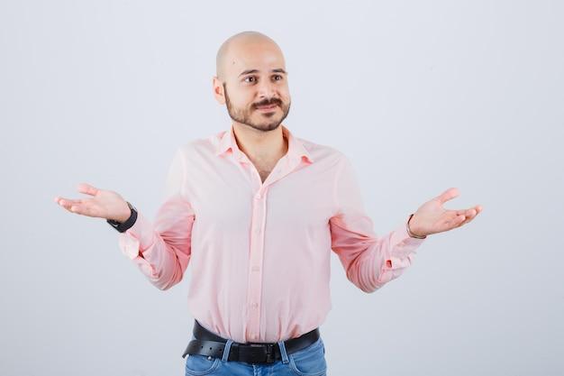 Młody mężczyzna w koszuli, dżinsach pokazujących bezradny gest i patrząc zmartwiony, widok z przodu.