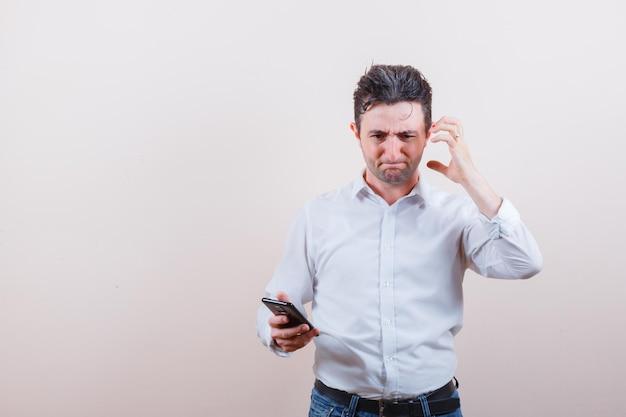 Młody mężczyzna w koszuli, dżinsach trzymających telefon komórkowy i patrzący z żalem
