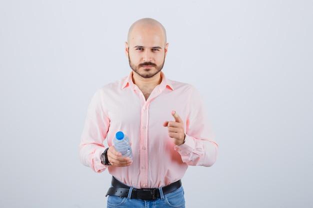 Młody mężczyzna w koszuli, dżinsach, wskazując aparat i patrząc pewnie, widok z przodu.