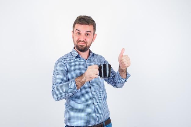 Młody mężczyzna w koszuli, dżinsy trzymając kubek, pokazując kciuk do góry i patrząc szczęśliwy, widok z przodu.