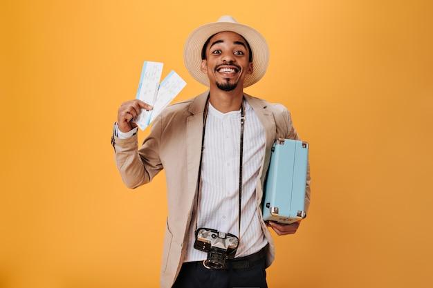 Młody mężczyzna w koszuli i kapeluszu trzymający bilety i walizkę