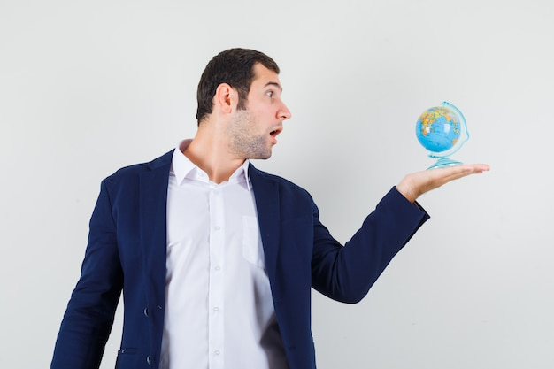 Młody mężczyzna w koszuli i kurtce patrząc na szkolnej kuli ziemskiej i patrząc zdziwiony