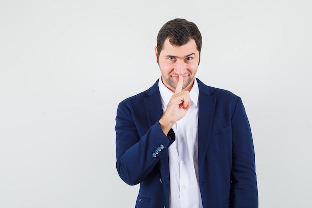 Młody mężczyzna w koszuli i kurtce pokazując gest ciszy i wyglądający pewnie