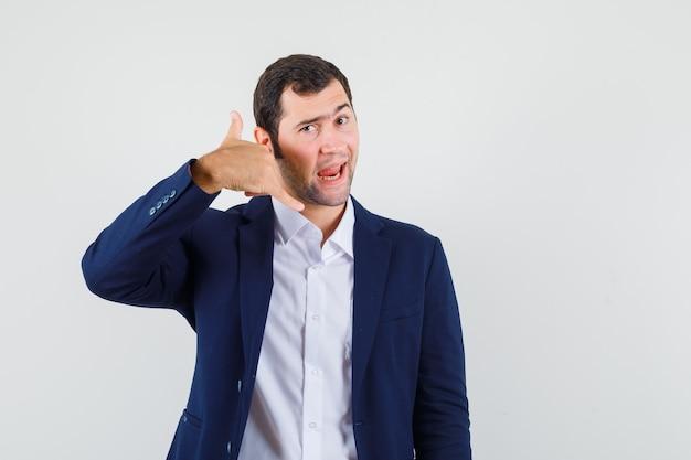 Młody mężczyzna w koszuli i kurtce pokazując gest telefonu i wyglądający fajnie