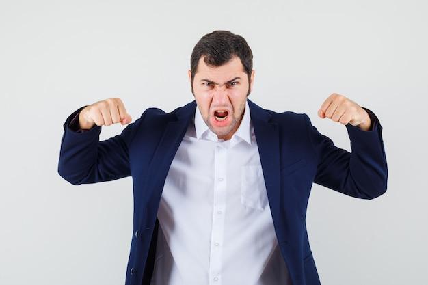 Młody mężczyzna w koszuli i kurtce pokazujący mięśnie ramion i wyglądający na potężnego