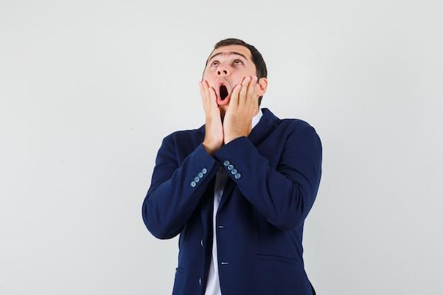 Młody mężczyzna w koszuli i kurtce, trzymając się za ręce na policzkach i patrząc zdziwiony