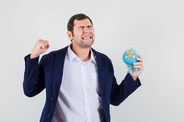 Młody mężczyzna w koszuli i kurtce, trzymając szkolną kulę ziemską i patrząc na szczęście