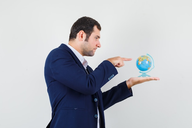 Młody mężczyzna w koszuli i kurtce, wskazując na szkolnej kuli ziemskiej i patrząc skupiony.
