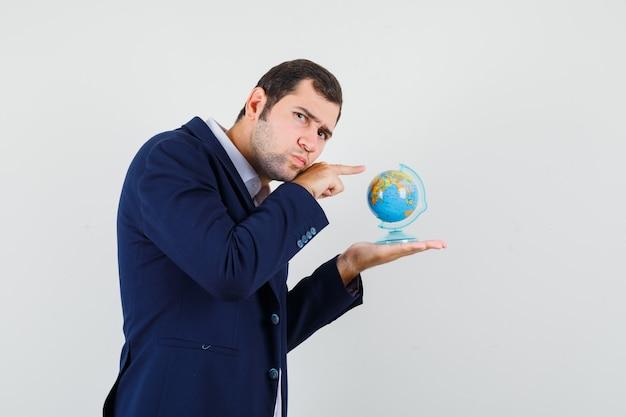 Młody mężczyzna w koszuli i kurtce, wskazując na szkolnej kuli ziemskiej i patrząc zamyślony.