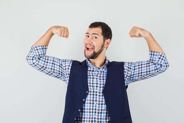 Młody mężczyzna w koszuli, kamizelce, pokazujący swoje mięśnie i wyglądający na potężnego, widok z przodu.