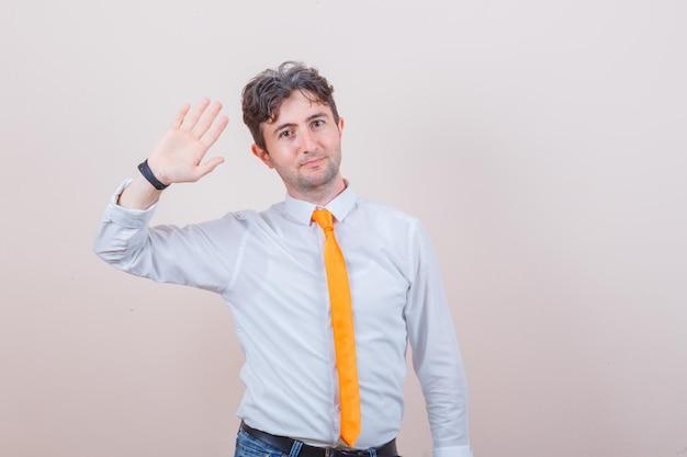 Młody mężczyzna w koszuli, krawacie, dżinsach macha ręką, aby się przywitać lub pożegnać i wygląda wesoło