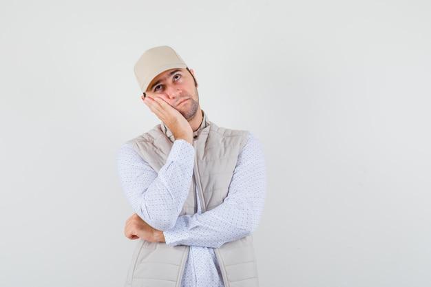 Młody mężczyzna w koszuli, kurtce bez rękawów, czapce pochylonej nad dłonią, myśląc i patrząc zamyślony, widok z przodu.