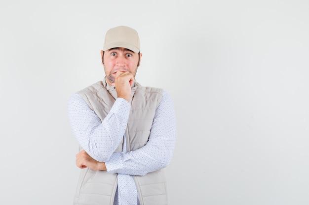 Młody mężczyzna w koszuli, kurtce bez rękawów, czapce trzymającej pięść na opuszczonej szczęce i wyglądający na podekscytowanego, widok z przodu. miejsce na tekst