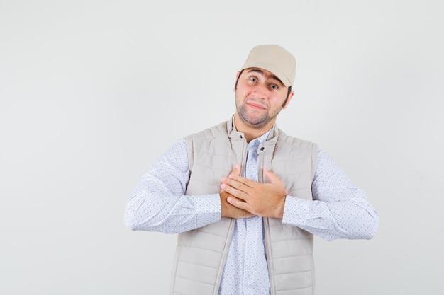 Młody mężczyzna w koszuli, kurtce bez rękawów, czapce trzymającej się za ręce na piersi i patrząc wdzięczny, widok z przodu.