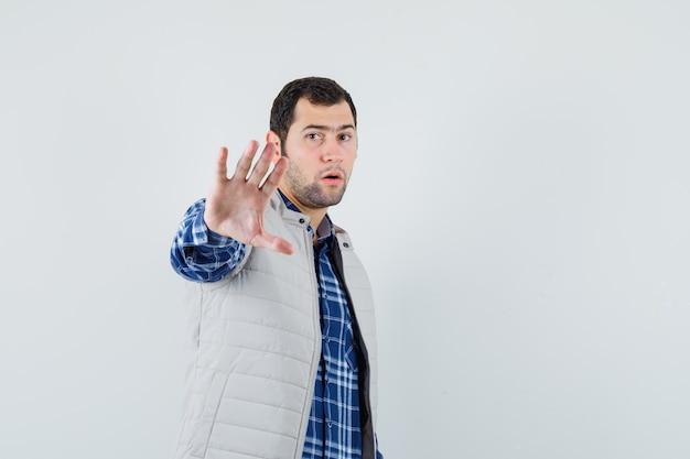 Młody mężczyzna w koszuli, kurtce bez rękawów, pokazując gest stop i patrząc skupiony, widok z przodu. miejsce na tekst