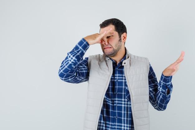 Młody mężczyzna w koszuli, kurtce bez rękawów, ściskając nos i wyglądając na zniesmaczonego, widok z przodu.