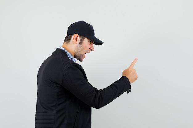 Młody mężczyzna w koszuli, kurtce, czapce ostrzega palcem, krzyczy i patrzy zdenerwowany.