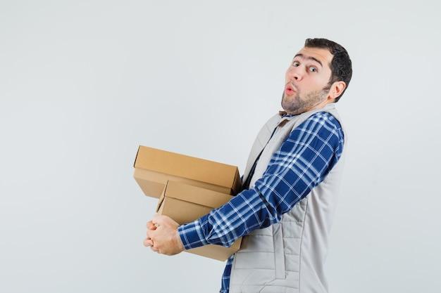 Młody mężczyzna w koszuli, kurtce, pudełkach i patrząc ciężko, widok z przodu.