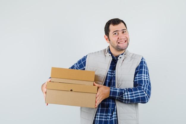 Młody mężczyzna w koszuli, kurtce, pudełkach i wyglądający na zadowolonego, widok z przodu.