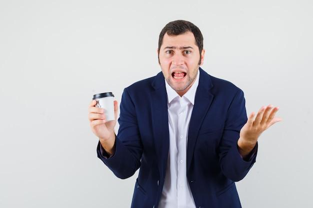 Młody mężczyzna w koszuli, kurtce, trzymając filiżankę kawy i patrząc zły