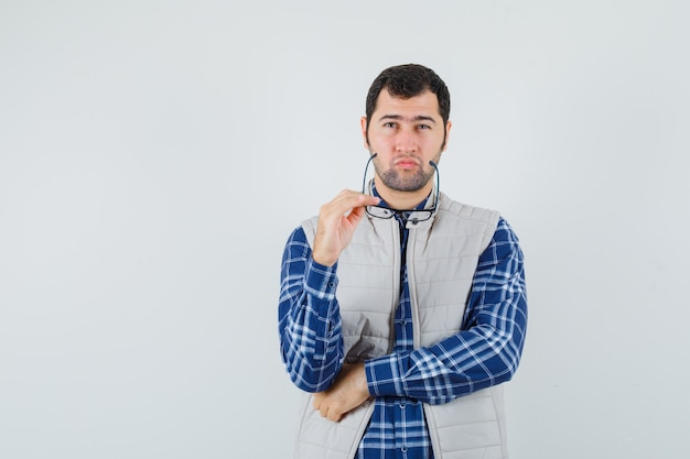 Młody mężczyzna w koszuli, kurtce trzymając okulary podczas myślenia i patrząc zamyślony
