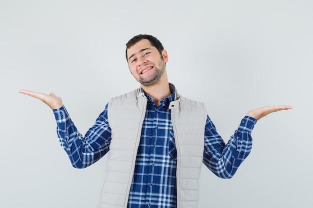 Młody mężczyzna w koszuli, kurtce z otwartymi dłońmi i wyglądającym na zadowolonego, widok z przodu.