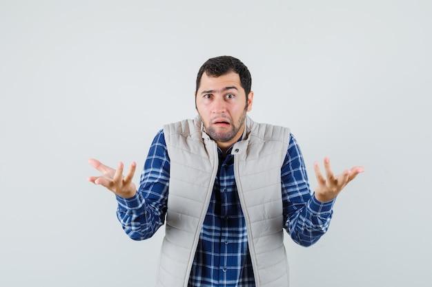 Młody mężczyzna w koszuli, kurtka bez rękawów pokazujący bezradny gest, widok z przodu.
