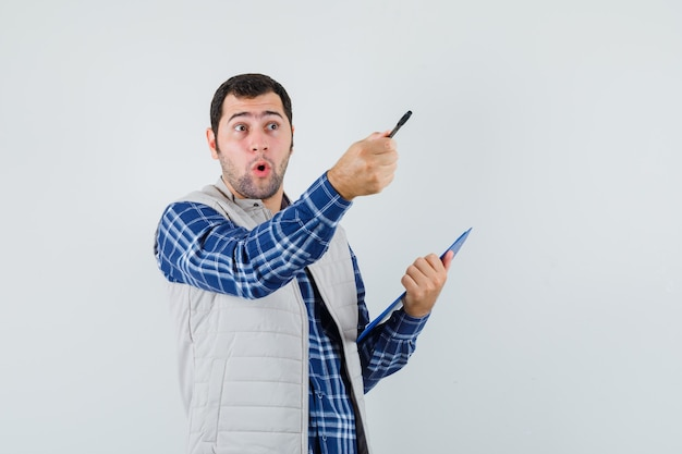 Młody mężczyzna w koszuli, kurtka, wskazując piórem i patrząc zdziwiony, widok z przodu.