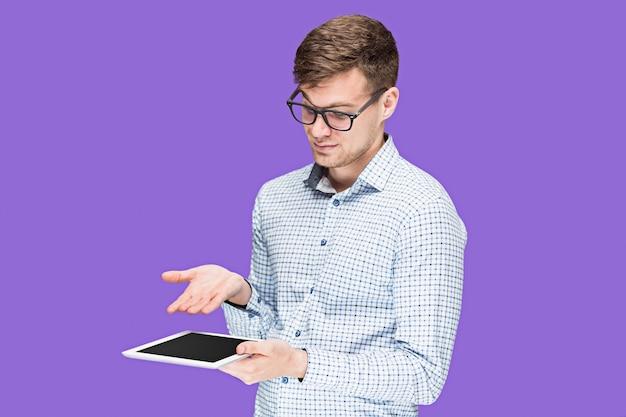 Młody mężczyzna w koszuli pracuje na laptopie na tle liliowego studia