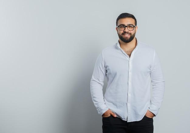 Młody mężczyzna w koszuli, spodnie trzymające się za ręce w kieszeniach i wyglądający na pewnego siebie